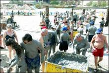 游客在死海抹黑泥